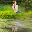 The girl sits on the bank of wood lake — Stock Photo