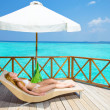 Young woman tans on villa on ocean Maldives — Stock Photo #3762521