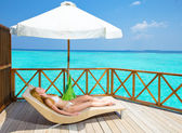 Young woman tans on villa on ocean Maldives — Stock Photo