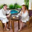 Young pair on romantic rest about pool behind a table with fruit — Stock Photo #3799557