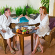 Young pair on romantic rest about pool behind a table with fruit — Stock Photo