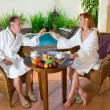 Young pair on romantic rest about pool behind a table with fruit — Stock Photo #3799564