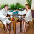 Young pair on romantic rest about pool behind a table with fruit — Stock Photo #3799582