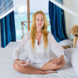 The young beautiful woman meditates on beds, ocean on a background in a win — Stock Photo #3799709
