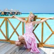 Young beautiful girl in pink sundress on platform of villa on water, Maldiv — Stock Photo #3911999