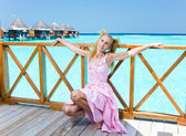 Young beautiful girl in pink sundress on platform of villa on water, Maldiv — Stock Photo