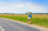 Beautiful young woman with luggage on road — Stock Photo