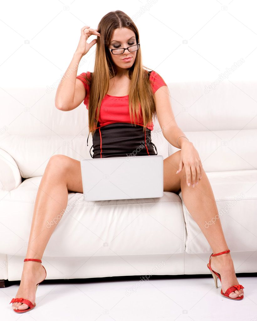 Beautiful young woman with glasses using laptop on sofa.  Stock Photo #3404491