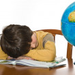 Tired boy sleeping while doing homework — Stock Photo