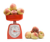 Red kitchen scale weighting peaches — Stock Photo