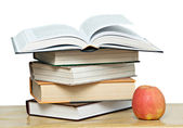 Red apple and open book on desk — Stock Photo