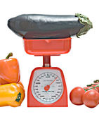 Kitchen scale weighting eggplant — Stock Photo