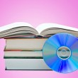 Pile of books, open book, and DVD disk as symbols of old and ne — Stock Photo