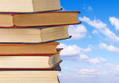 Pile of books on sky background — Stock Photo