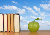 Green apple and books — Stock Photo
