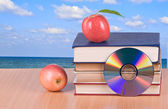 Apple, dvd, and books as a symbol of transition from old to new — Stock Photo