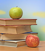 Red and green apple and books on desk — Stockfoto