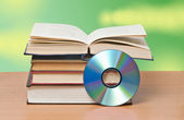 Open book and DVD disk as symbols of old and new methods of inf — Stock Photo
