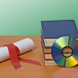 Scroll with red ribbon and books — Stock Photo