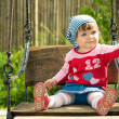 Beautiful child on the swings - Stock Photo