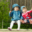 Two children on the swings in park — Stock Photo