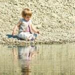 dziewczynka siedzi na kamienie plaży — Zdjęcie stockowe