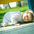 Girl plays hide and seek under bench — Stock Photo