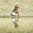 Little girl sitting on a stones-beach — Stock fotografie