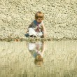Little girl sitting on a stones-beach — Stock fotografie #2763340