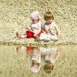 Stock Photo: Little girls sitting on a stones-beach