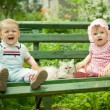 Boy and girl on the bench in park - Stok fotoğraf
