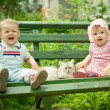Boy and girl on the bench in park - Stockfoto