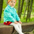 Royalty-Free Stock Photo: Young baby sits on a wooden bench