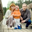 Happy family on a wooden bridge — Stock Photo