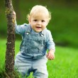 Little happy child near the tree - Foto Stock