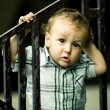 Little boy behind the fence - Stock Photo