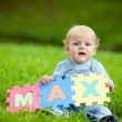 Boy holds puzzles with name Max — Stock Photo #2764056