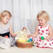 Stock Photo: Two girls play with a basket of eggs