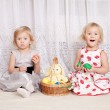 Two girls play with a basket of eggs — Stock Photo
