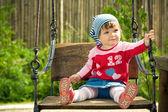 Beautiful child on the swings — Stock Photo