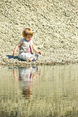 Little girl sitting on a stones-beach — Stock Photo