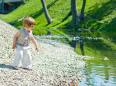 Little girl on a stones-beach — Stock Photo