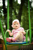 Beautiful child on the swings — Stock Photo