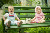 Boy and girl on the bench in park — 图库照片