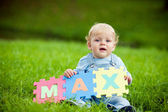Boy holds puzzles with name Max — Stock Photo