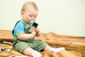 Baby looks at mobile phone with interest — Stock Photo