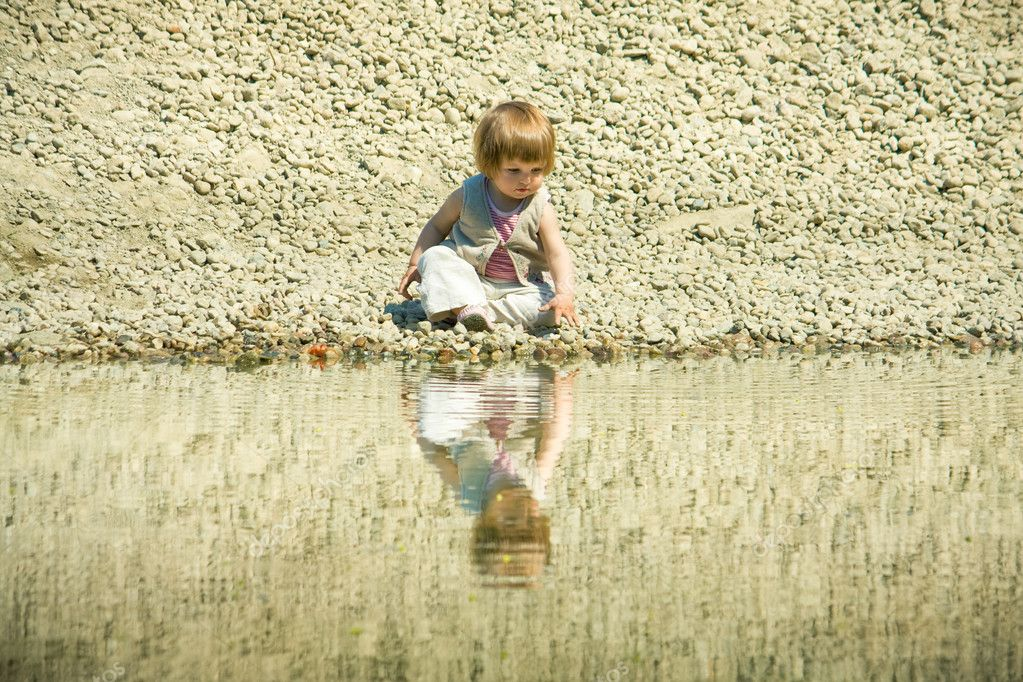 Little girl sitting on a stones-beach near water  Stock Photo #2763340