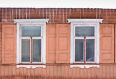 Two aged windows and icicle — Stock Photo