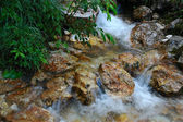 Small clear brook running beside stones — Stock Photo