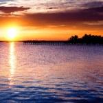 Dramatic sunrise over river pier. — Stock Photo
